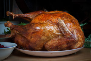 Perfectly roasted turkey sitting o a serving plate.