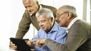 Three senior men looking at a tablet.