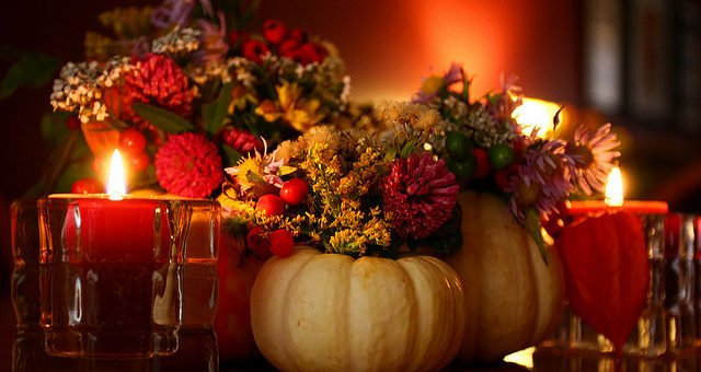 Thanksgiving centerpiece with candles and pumpkins.
