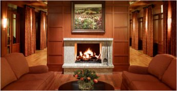 Fireplace with fire in wood paneled room with plush couches.