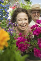 Senior Couple Surrounded by Flowers in a bright vibrant garden.