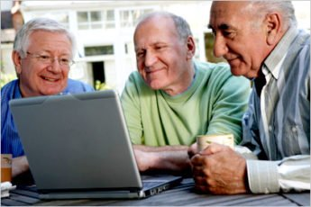 Three older men gather around a laptop computer to see the screen.