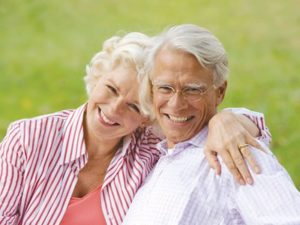 A senior citizen couple pose smiling outside on a green lawn.