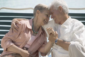 A senior couple holds hands with their heads together as they sit on lawnchairs.