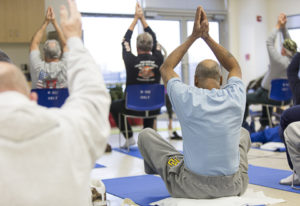 Seniors practicing yoga warrior pose in the seated position